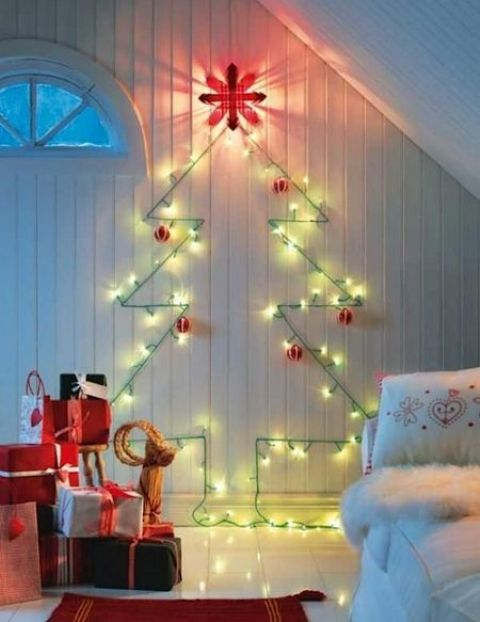 a cute wall-mounted Christmas tree done with green lights and red and white ornaments for a traditional feel