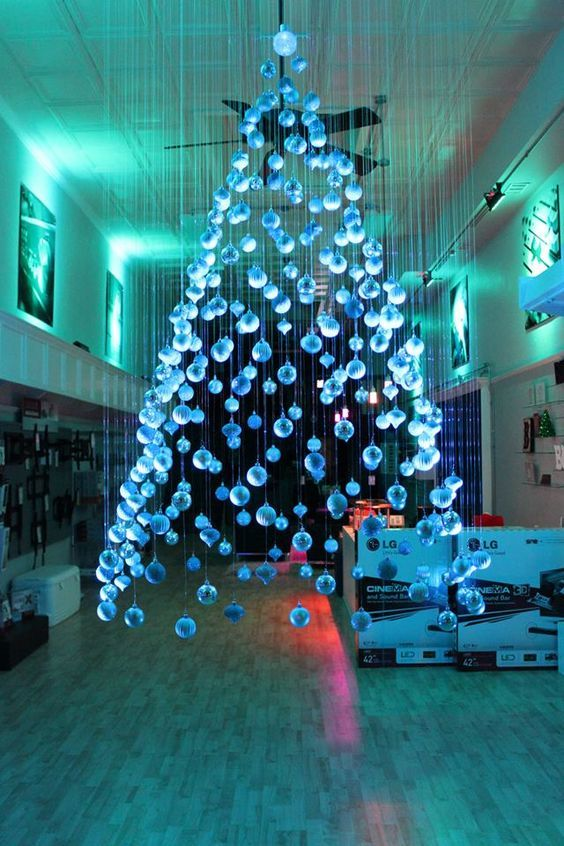 a large and beautiful ice blue suspended Christmas tree of ornaments floating above the floor