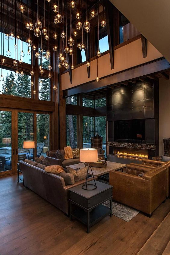 a modern rustic luxurious home with a double height ceiling and a whole hanging light installation