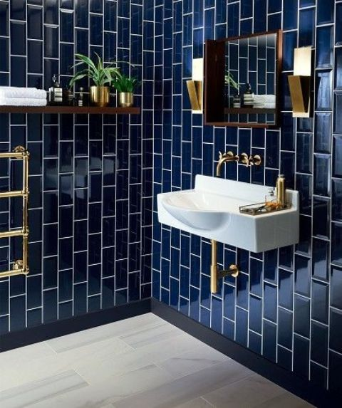 a navy tiled bathroom with white grout and gold fixtures looks timelessly elegant, gold metal features fit both masculine and feminine rooms