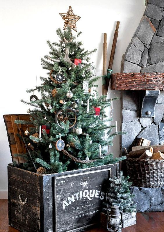 a rustic Christmas tree with antlers, wood slice ornaments, a twig star on top, branches and an antique crate as a base