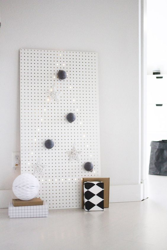 a white pegboard with a Christmas tree lined out with lights and with some ornaments