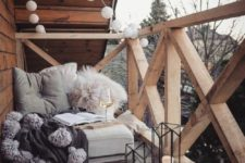 02 candle lanterns, lights garlands, a seat with fluffy pillows and tassel blanket for a contemporary terrace look