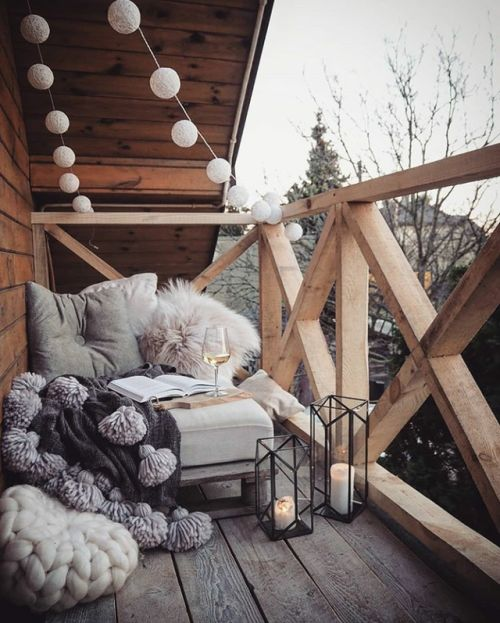 candle lanterns, lights garlands, a seat with fluffy pillows and tassel blanket for a contemporary terrace look