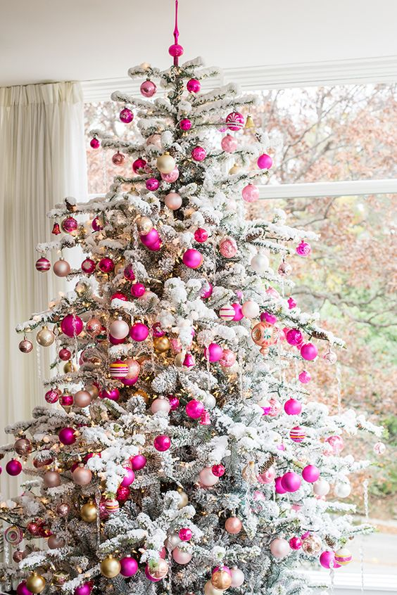 super bold fuchsia and gold ornaments stand out a lot on a flocked tree