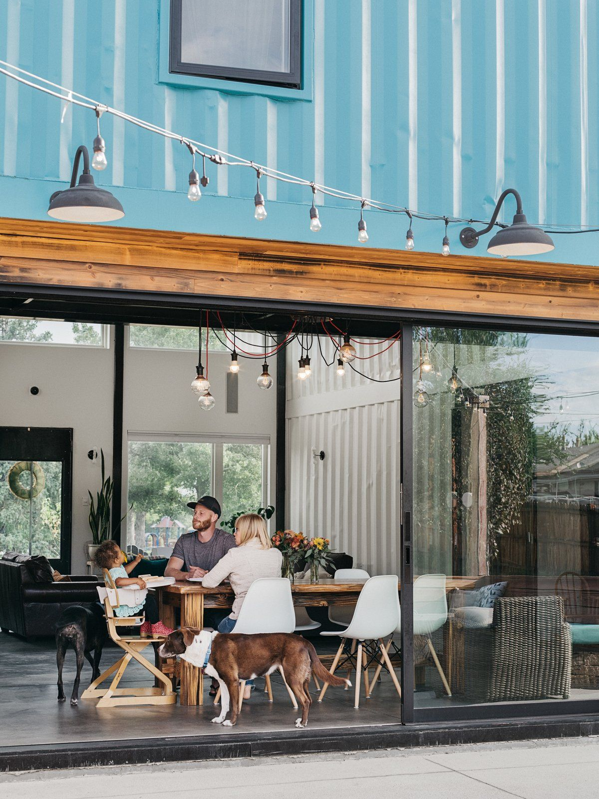 The dining space is done with a wooden table, modern chairs and with bulbs over the dining set