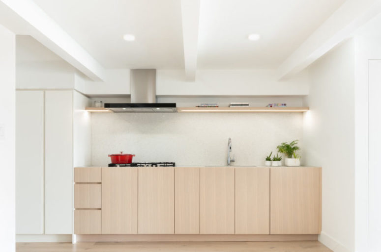 The kitchen is a minimalist space done with light-colored cabinets and white ones, with a neutral backsplash