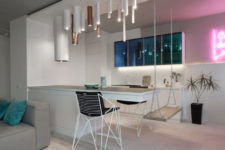 03 The kitchen island features a diing space and a swing as a seat