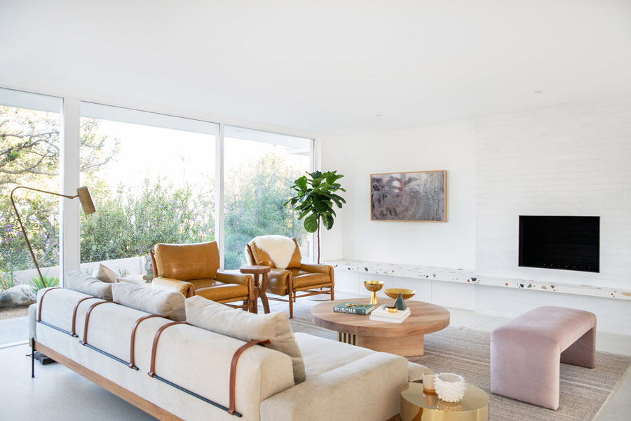 The living room is an airy space, there's neutral comfy furniture, a terrazzo shelf and side tables