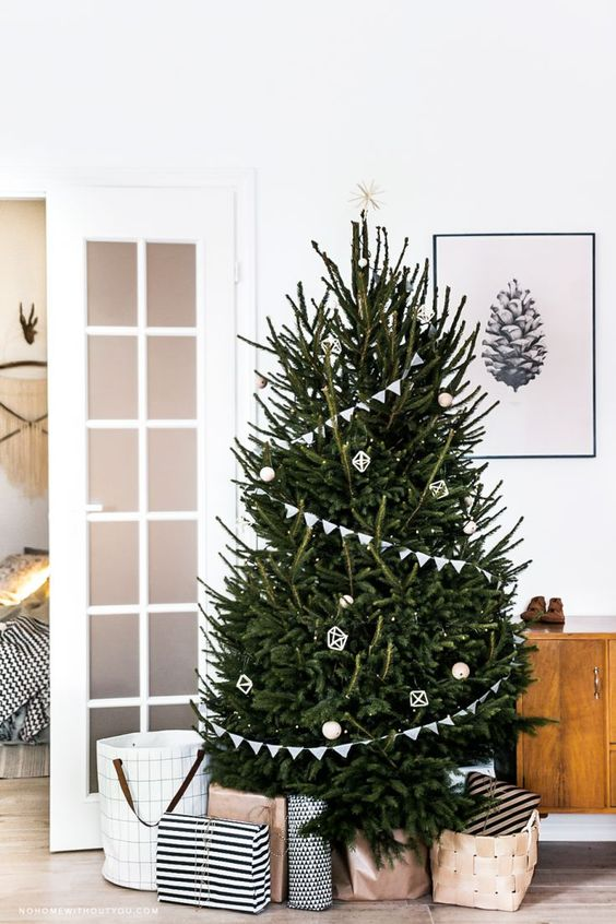 a modern Scandi tree with buntings, white and wooden ornaments and a star on top plus lights