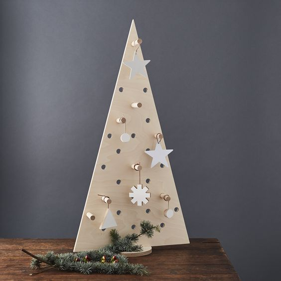 a pegboard Christmas tree with plywood ornaments hanging on hooks is an ultra-modern idea to DIY