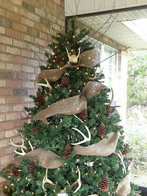 a rustic feel is brought with burlap ribbons, pinecones, antlers and lights is a cozy outdoor decoration