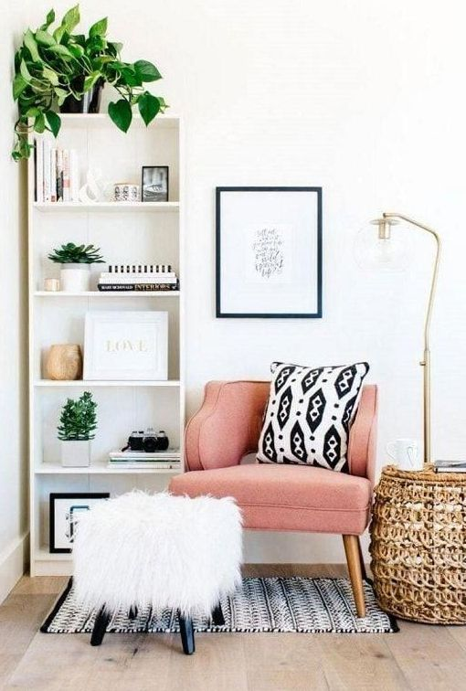 a shelving unit, a comfy chair with a fluffy footrest, a wicker coffee table and a floor lamp