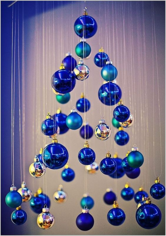 a small Christmas tree of matte and shiny blue ornaments and little silver ones is a whimsy and creative DIY idea