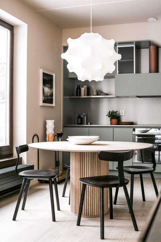 a soft pastel minimalist kitchen in blush, beige and with touches of muted green plus black chairs