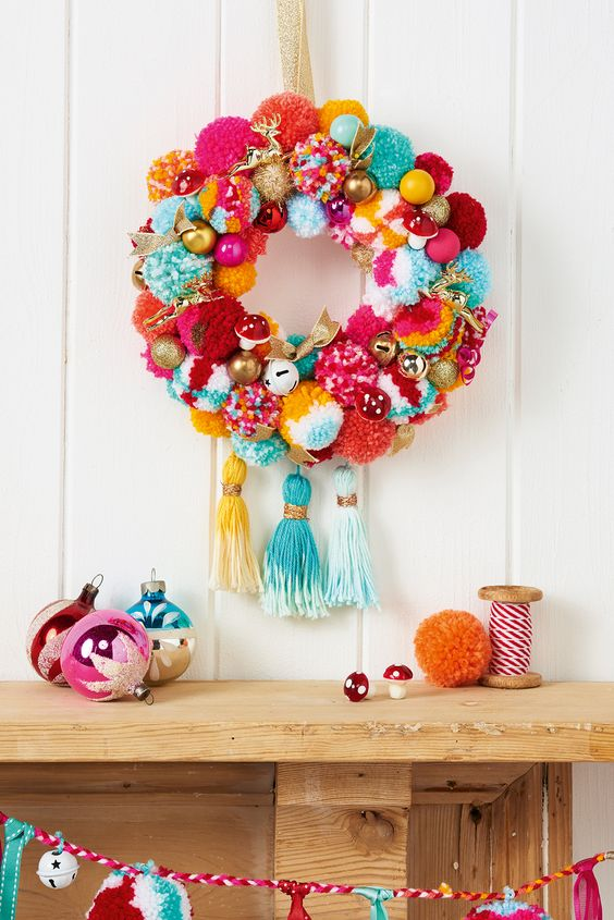 a super colorful and whimsy holiday wreath with pompoms, ornaments, fake mushrooms and large tassels