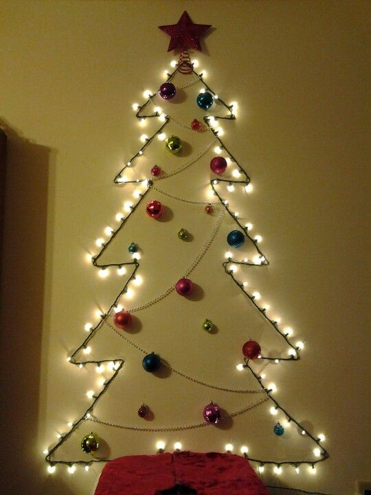 a wall-mounted tree made of lights, beads and colorful ornaments plus a glitter star for an entryway or another space