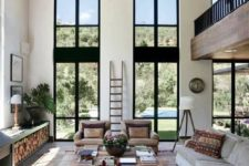 03 a welcoming modern rustic living room in neutrals, with double height windows and an airy feeling