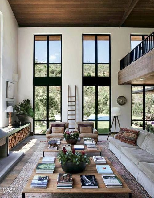 a welcoming modern rustic living room in neutrals, with double height windows and an airy feeling