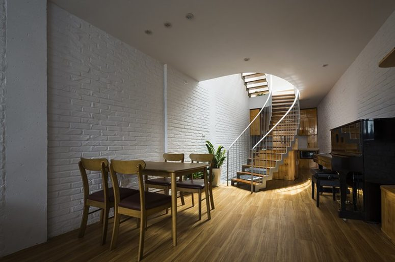 The dining space and kitchen are united in one space, the kitchen is hidden behind the stairs, and there's a piano
