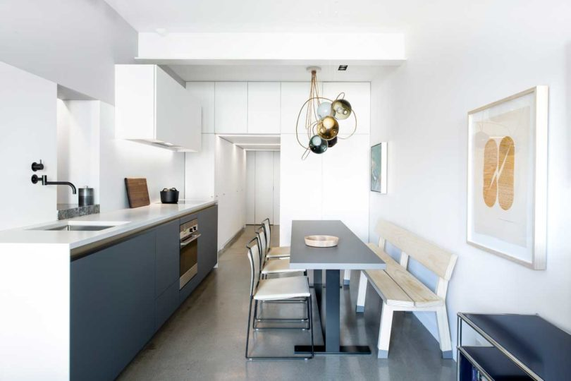 The kitchen is combined with the dining zone and the space looks super laconic and stylish