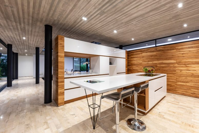 The kitchen is done with sleek white cabinets, it's separated with a half wall from the dining space