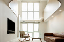 04 The living room is double-height, with super tall windows, there's just a sofa, chair and a coffee table