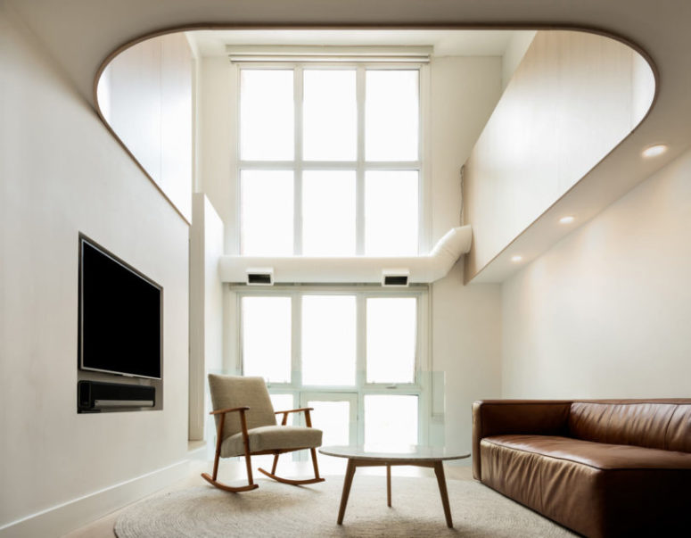 The living room is double-height, with super tall windows, there's just a sofa, chair and a coffee table