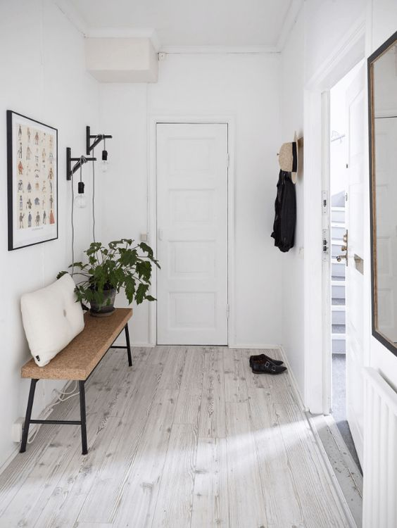 a Scandinavian entryway with whitewashed floors and a cork bench feels minimal and airy
