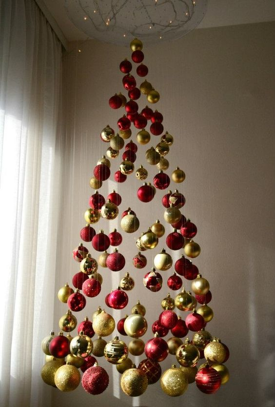 a chic Christmas tree of red and gold glitter, shiny and matte ornaments and lights above it