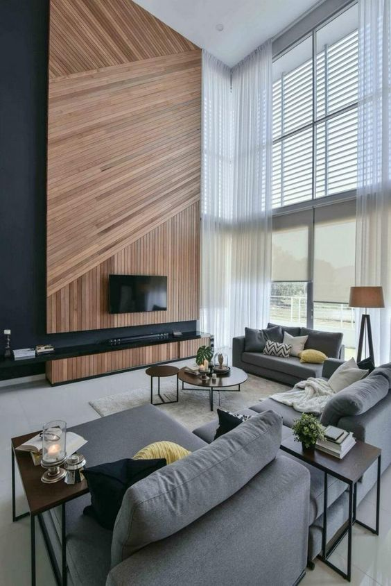 a gorgeous contemporary space with oversized windows, a geometric wood clad TV wall and comfy furniture