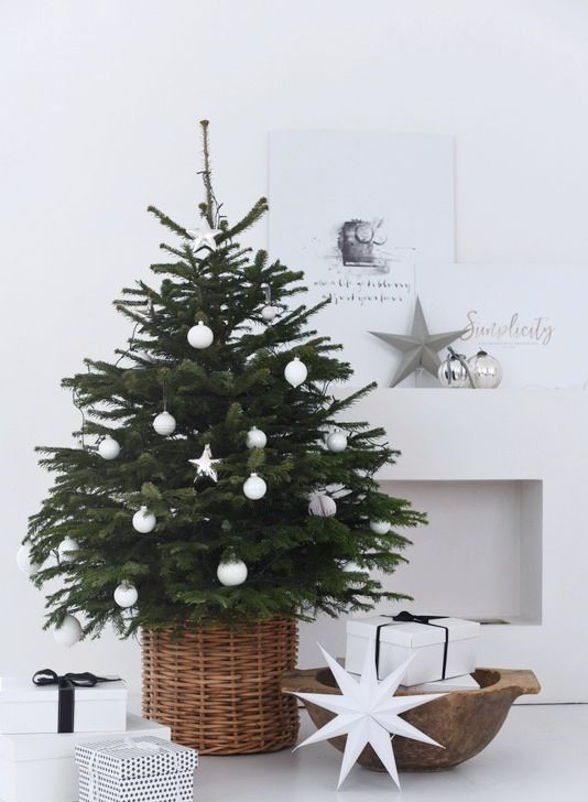 a modern Scandinavian Christmas tree with white ball and star ornaments in a basket looks very laconic and chic