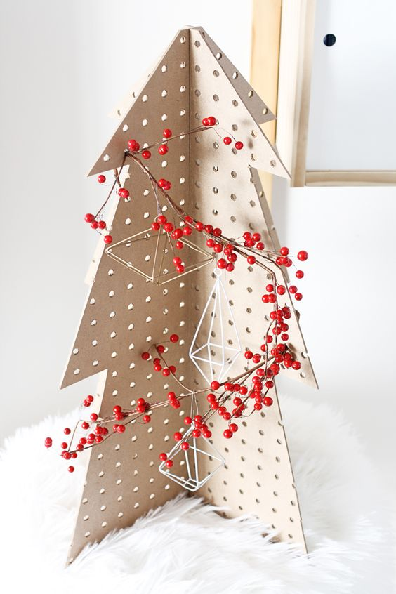 a pegboard Christmas tree decorated with himmeli ornaments and berries placed on faux fur is a great tabletop idea