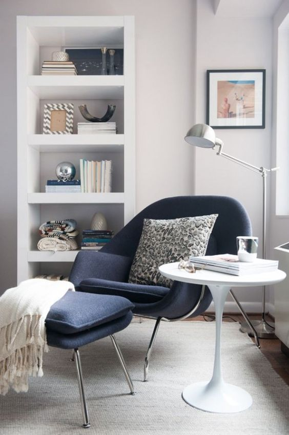 a shelving unit, a comfy chair with a matching footrest, a coffee table and a metal floor lamp that matches the chair frame