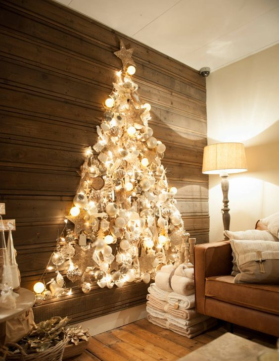 a shiny wall-mounted Christmas tree made with lights on the contour and with lots of silver, pearly and white ornaments inside