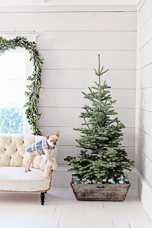 a small Christmas tree placed into a wooden crate filled with emerald ornaments is a modern farmhouse idea