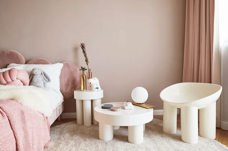 The kid's room is done in neutrals and tender pink tones, gilded touches add a glam feel