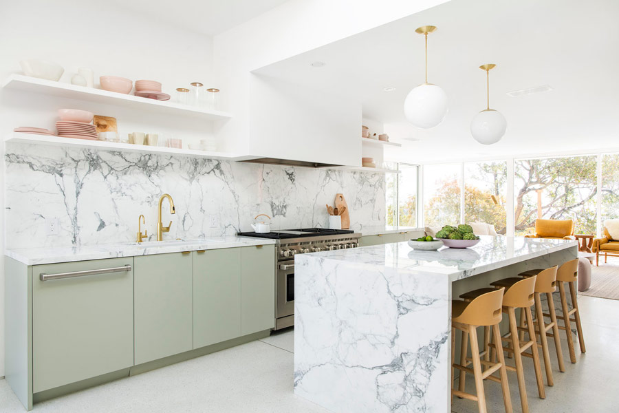 The kitchen is done with light green cabinets and the surfaces are covered with stone