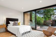 05 The master bedroom features a comfy bed, several bedside tables, a contemporary chair and a glazed wall with an entrance to the garden
