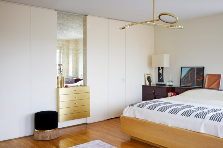 The master bedroom is done in light shades, light-colored wood, a metallic built-in vanity and much closed storage