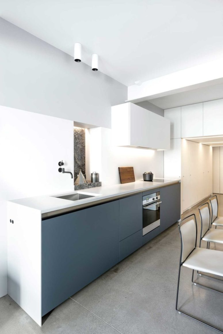 The minimalist kitchen features lower grey cabinets and white countertops, some more white storage units