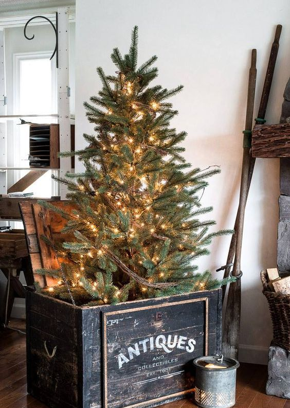 a Christmas tree placed into a vintage black crate and decorated with lights only is a cool rustic and vintage idea