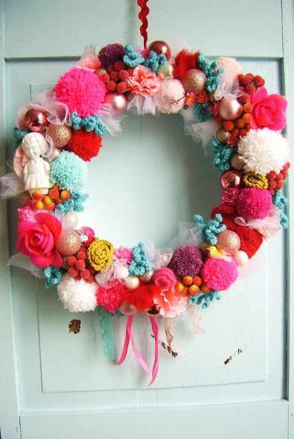 a colorful and whimsy Christmas wreath of pompoms, fake birds, ornaments, ribbons and roses