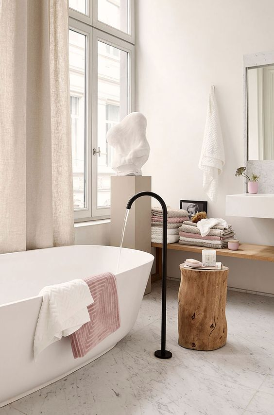 a contemporary bathroom with stone and wood, touches of blush and dusty pink for a girlish feel