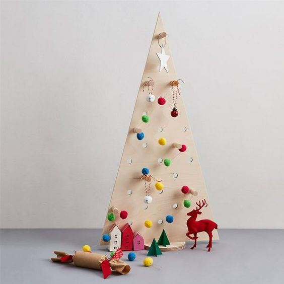 a little pegboard Christmas tree with pompom and jingle bell ornaments hanging on hooks
