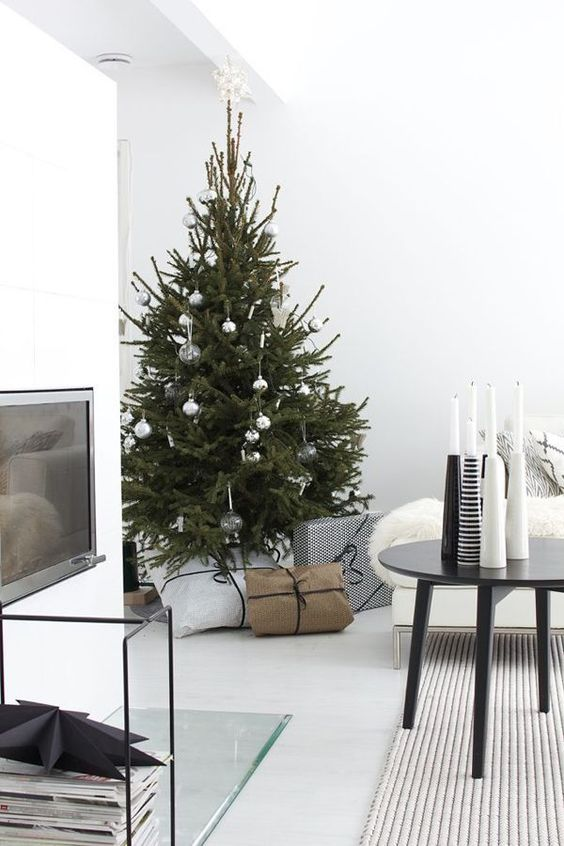a modern Scandi Christmas tree with white, clear and metallic ornaments and no lights for a laconic look