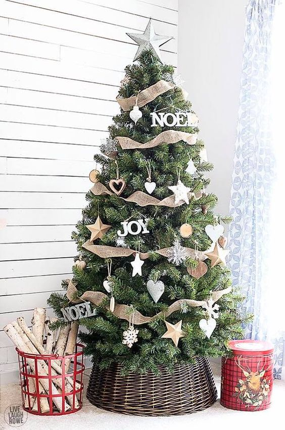 a super cozy Christmas tree with various star ornaments including wooden ones, burlap ribbons, snowflakes and hearts plus a basket cover