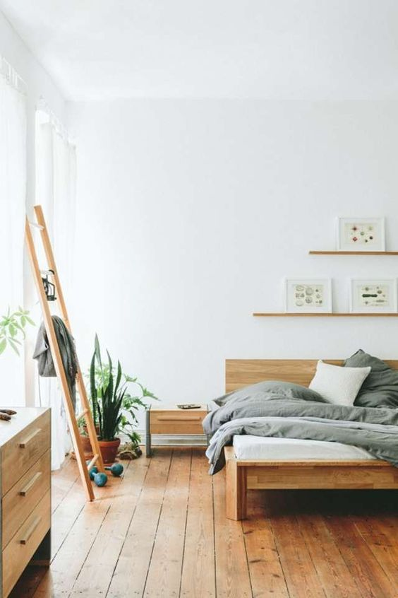 this minimalist bedroom looks very warm and welcoming due to a large amount of wood used in decor