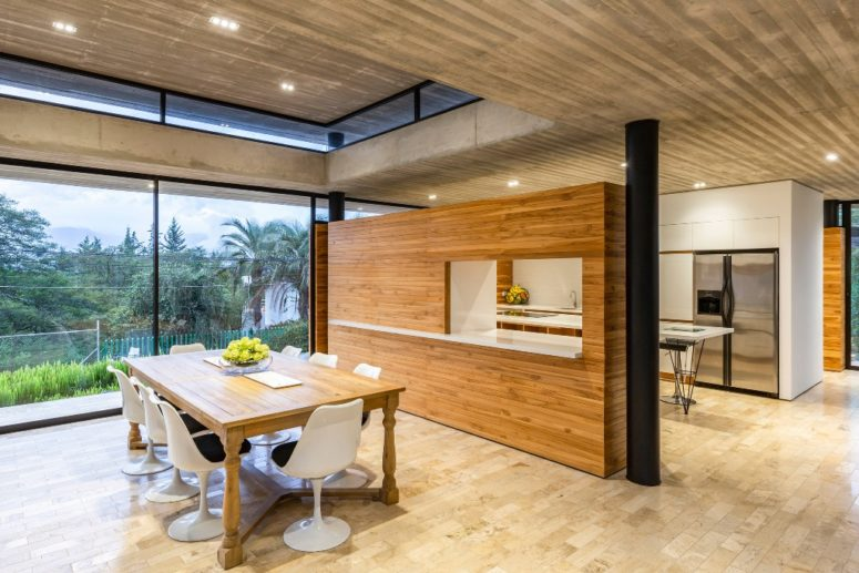 The dining space is done with modern white chairs and a wooden table