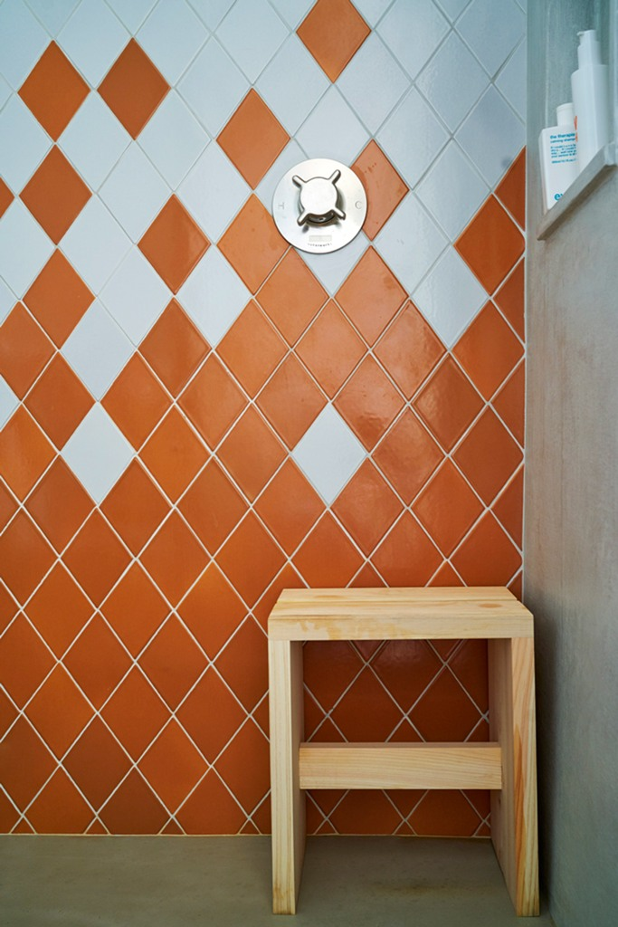 The master bathroom is done in orange and white tiles shaped as diamonds to highlight the jewelry inspiration